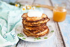 Healthy breakfast with oatmeal pancakes and honey. Breakfast: oatmeal pancakes with sour cream and honey. On wood table with tablecloth Stock Image