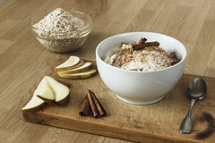Healthy breakfast with oatmeal, pear, apple, coconut milk and cinnamon Royalty Free Stock Photo
