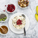 Healthy breakfast oatmeal with pomegranate, bananas, seeds and nuts, overhead scene on white marble. Top view. Healthy breakfast oatmeal with pomegranate Royalty Free Stock Photography