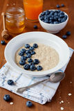 Healthy breakfast of oatmeal porridge, berries, honey and fresh juice Stock Images