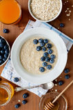 Healthy breakfast of oatmeal porridge, berries, honey and fresh juice Royalty Free Stock Image