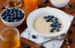 Healthy breakfast of oatmeal porridge, berries, honey and fresh juice Stock Image