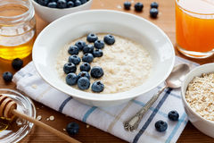 Healthy breakfast of oatmeal porridge, berries, honey and fresh juice Stock Photography