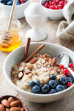 Healthy breakfast Oatmeal porridge with berries, nuts and honey stock photography
