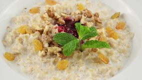 Healthy breakfast, oatmeal porridge, raisins, walnuts and milk (loop) stock video footage