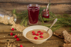 Healthy breakfast, Oatmeal porridge with raspberries and beverag. Oatmeal porridge with raspberries and compote on the wooden table Royalty Free Stock Images