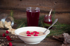Healthy breakfast, Oatmeal porridge with raspberries and beverag. Oatmeal porridge with raspberries and compote on the wooden table Stock Photo