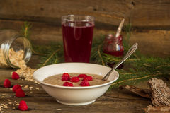 Healthy breakfast, Oatmeal porridge with raspberries and beverag. Oatmeal porridge with raspberries and compote on the wooden table Royalty Free Stock Photography
