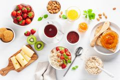 Healthy breakfast with oatmeal porridge, strawberry, nuts, toast. Jam and tea. Top view royalty free stock photo