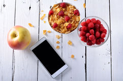 Healthy breakfast, oatmeal with raspberries, a glass of milk, an. Apple and mobile phone on a wooden table. Kontseptsmya healthy diet Royalty Free Stock Image