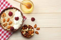 Healthy breakfast. oatmeal, raspberries, honey and nuts on white wooden table. Top view with copy space Royalty Free Stock Image