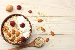 Healthy breakfast. oatmeal, raspberries and nuts on white wooden table. Top view with copy space Stock Photography