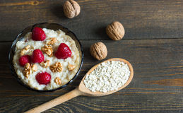 Healthy breakfast, oatmeal with raspberries and walnuts. On wooden table Stock Photo