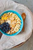 Healthy breakfast with oats and fruits. Delicious healthy breakfast with oats, berries, almonds, banana, peanut butter and cereals with wooden spoon stock image