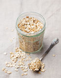 Healthy breakfast Organic oat flakes in a glass jar Grey textile background. Stock Images