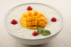 Healthy  Breakfast . - Organic rice pudding with yellow mango and coconut. Mango rice pudding. Royalty Free Stock Photography