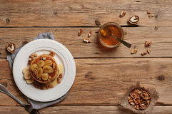 Healthy breakfast of pancakes with honey, nuts and caramelized b. Delicious and healthy breakfast of pancakes with honey, nuts and caramelized bananas on wooden Royalty Free Stock Photography