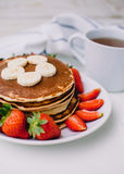 Healthy breakfast. Pancakes with strawberries, bananas, cup of black tea on white background with white towel. Healthy breakfast. Pancakes with strawberries Stock Photography