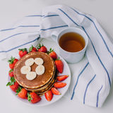 Healthy breakfast. Pancakes with strawberries, bananas, cup of black tea on white background with white towel. Healthy breakfast. Pancakes with strawberries Royalty Free Stock Photo