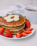 Healthy breakfast. Pancakes with strawberries, bananas, cup of black tea on white background with white towel. Healthy breakfast. Pancakes with strawberries Royalty Free Stock Images