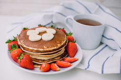 Healthy breakfast. Pancakes with strawberries, bananas, cup of black tea on white background with white towel. Healthy breakfast. Pancakes with strawberries Stock Photos