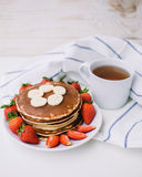 Healthy breakfast. Pancakes with strawberries, bananas, cup of black tea on white background with white towel. Healthy breakfast. Pancakes with strawberries Royalty Free Stock Photography