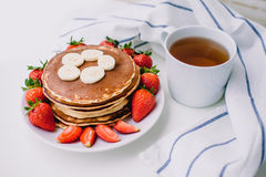Healthy breakfast. Pancakes with strawberries, bananas, cup of black tea on white background with white towel. Healthy breakfast. Pancakes with strawberries Stock Image