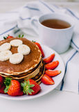 Healthy breakfast. Pancakes with strawberries, bananas, cup of black tea on white background with white towel. Healthy breakfast. Pancakes with strawberries Royalty Free Stock Photos