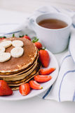 Healthy breakfast. Pancakes with strawberries, bananas, cup of black tea on white background with white towel. Healthy breakfast. Pancakes with strawberries Stock Photo