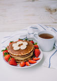 Healthy breakfast. Pancakes with strawberries, bananas, cup of black tea on white background with white towel. Healthy breakfast. Pancakes with strawberries Stock Images