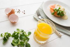 Healthy breakfast with poached eggs. Healthy breakfast with fresh orange juice, salad and poached eggs with salmon on a white wooden table stock image