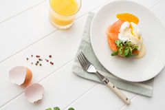 Healthy breakfast with poached eggs. Healthy breakfast with fresh orange juice, salad and poached eggs with salmon on a white wooden table Stock Images