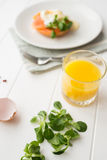 Healthy breakfast with poached eggs. Healthy breakfast with fresh orange juice, salad and poached eggs with salmon on a white wooden table royalty free stock photos