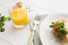 Healthy breakfast with poached eggs. Healthy breakfast with fresh orange juice, salad and poached eggs with salmon on a white wooden table Stock Photos