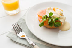 Healthy breakfast with poached eggs. Poached eggs royale with salmon, sauce hollandaise, salad and fresh orange juice Royalty Free Stock Photo