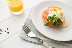Healthy breakfast with poached eggs. Poached eggs royale with salmon, sauce hollandaise, salad and fresh orange juice royalty free stock images