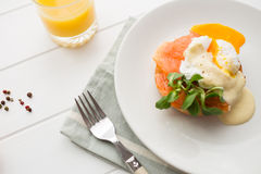 Healthy breakfast with poached eggs. Poached eggs royale with salmon, sauce hollandaise, salad and fresh orange juice stock photo