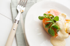 Healthy breakfast with poached eggs. Poached eggs royale with salmon, sauce hollandaise, salad and fresh orange juice Stock Photography
