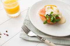 Healthy breakfast with poached eggs. Poached eggs royale with salmon, sauce hollandaise, salad and fresh orange juice Stock Images