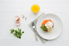 Healthy breakfast with poached eggs. Top view of healthy breakfast with poached eggs royale (benedict), fresh orange juice and green salad Stock Images
