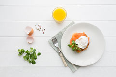 Healthy breakfast with poached eggs. Top view of healthy breakfast with poached eggs royale (benedict), fresh orange juice and green salad Stock Image