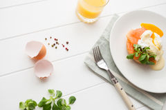 Healthy breakfast with poached eggs. Top view of healthy breakfast with poached eggs royale (benedict), fresh orange juice and green salad on a white wooden royalty free stock image