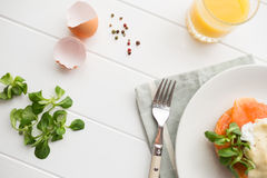 Healthy breakfast with poached eggs. Top view of healthy breakfast with poached eggs royale (benedict), fresh orange juice and green salad on a white wooden Royalty Free Stock Images
