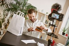Healthy breakfast. Positive food blogger holding a plate with fresh sandwich while recording new video for his vlog. Food concept. Gastronomy stock images