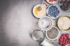 Healthy breakfast preparation with ingredients and empty glass jar on stone background, top view Stock Images