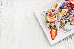 Healthy breakfast preparation: Muesli in jar with summer fresh berries, seeds and  nuts on light wooden background, top view Royalty Free Stock Image