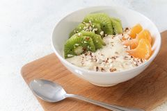 Healthy breakfast with protein from quark or curd cheese, linseed oil with omega 3 fatty acids, fresh fruits and nuts, budwig die. T in a white bowl on a wooden royalty free stock images