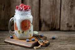 Healthy breakfast is pudding with chia seeds, agave syrup, milk, figs and frozen berries of raspberries and blueberries. Stock Photography