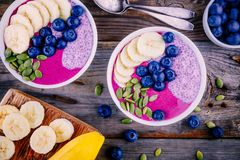 Healthy breakfast: purple smoothie bowl with chia pudding, banana, fresh blueberries and pumpkin seeds. On wooden background Royalty Free Stock Image