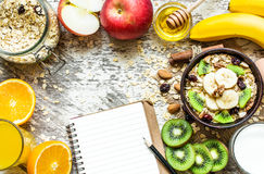 Healthy breakfast with recipe book. Healthy breakfast with fruit oatmeal, fresh fruits, honey, egg, milk and orange juice with recipe book. top view Royalty Free Stock Photography